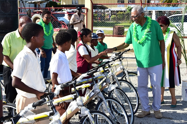 President David Granger greets a recipient of a bicycle gifted through the Public Education Transport Service (PETS).