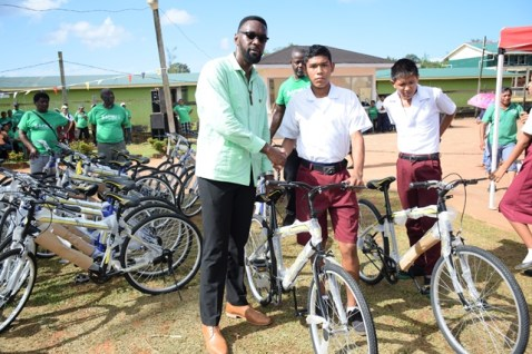 Director of Sport, Christopher Jones handing over a bicycle to one of the students.