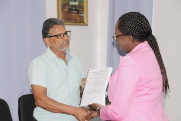 Minister of Education, Hon. Nicolette Henry and CEO of R.Bassoo and Sons Contracting Services, Mr. Roy Bassoo displaying the signed contract for the construction of the Westminster Secondary School.