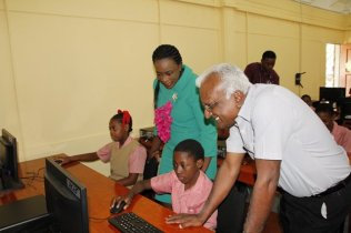 Minister of Education and MISU Head engaging students of Eccles Primary School in their IT Lab.