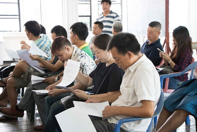 Chinese business owners, perusing copies of Guyana's Labour Laws.