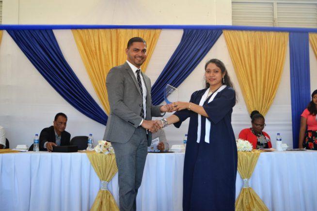 Neurosurgeon Dr. Amarnauth Dukhi hands over the trophy to top student and valedictorian Yugeeta Kumar