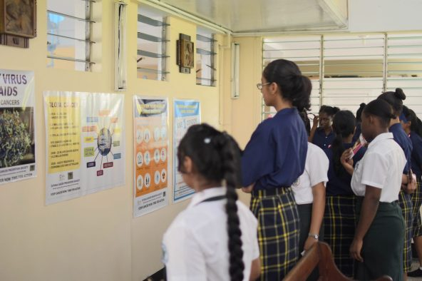 Students viewing a poster depicting the symptoms of cancer