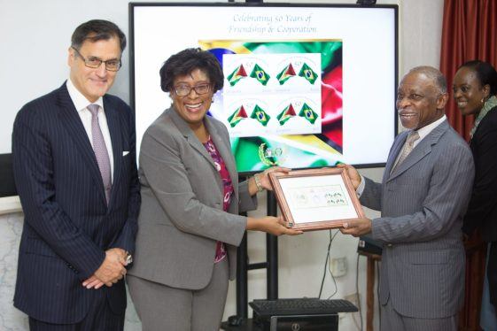 Minister of Public Telecommunications, Catherine Hughes presents Minister of Foreign Affairs, Carl Greenidge with the stamps as Deputy Head of Mission of the Embassy of Brazil, Paulo Silos looks on