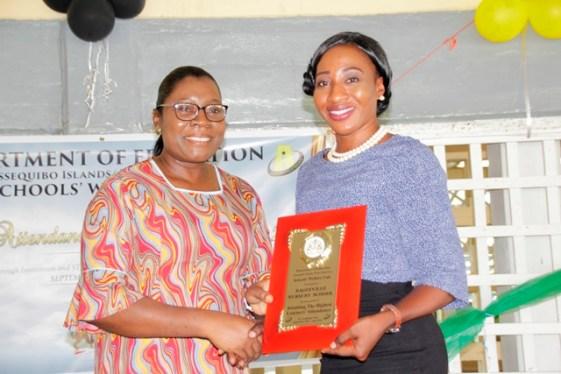 A teacher from Bagotville Nursery School receiving the award on behalf of the school from REdO, Annesta Douglas.