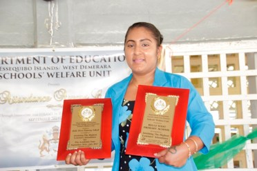 Rampattie Bisnauth, teacher of Belle West Primary School posing with the two plaques secured by the school for their exceptional attendance records over the past two years.