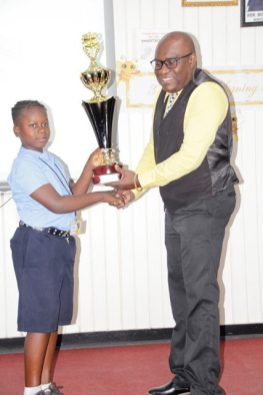 Troy Scott of the Linden Special Needs Centre receiving his first place trophy from the Chief Education Officer, Mr. Marcel Hutson.