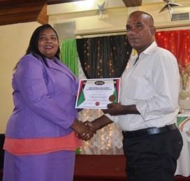 One of the graduates receiving their certificate from PTCCB Registrar, Trecia Garnath