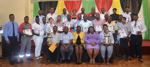 The graduates pose for a photo with some of the Ministry's officials at the graduation ceremony