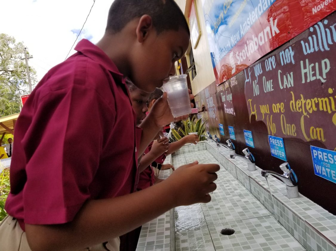 Students taking a drink of water from the newly installed purified water system