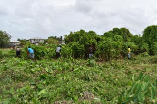 Sophia residents along with members of the Guyana Police Force tackling the overgrowth to clear the designated area where a sports ground will be constructed