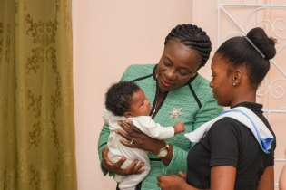 Minister of Education, Nicolette Henry conversing with a teen mom and her baby.