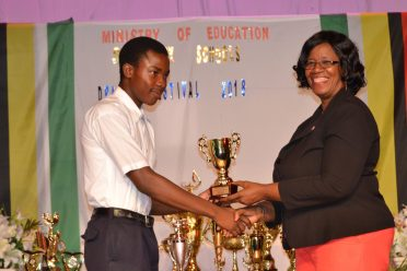 Nathan Wickham, of Uitvlugt Secondary, receiving his award for Most Promising Actor from Administrator (ag) of the Unit of Allied Arts, Lorraine Barker-King