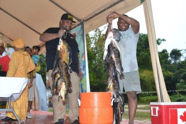 Ravin Persaud and Vickey Gordon holding up their catch.