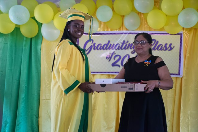 Wife of the Prime Minister, Mrs. Sita Nagamootoo presenting valedictorian, Tanya Semple with a laptop.