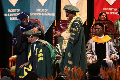Recipient of an honorary doctorate, Jairaj Sobhraj, takes a knee to allow Registrar of the University of Guyana, Nigel Gravesande, to complete his robing as Vice Chancellor, Professor Ivelaw Griffith, looks on.