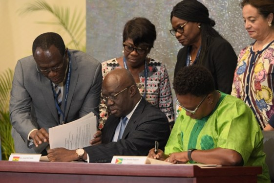Minister within the Ministry of Public Infrastructure, Annette Ferguson and Minister of Aviation of Ghana, Joseph Kofi Adda signing the agreement, flanked by delegates and officials.