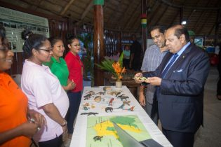 Prime Minister Nagamootoo examining an animal figurine made from balata