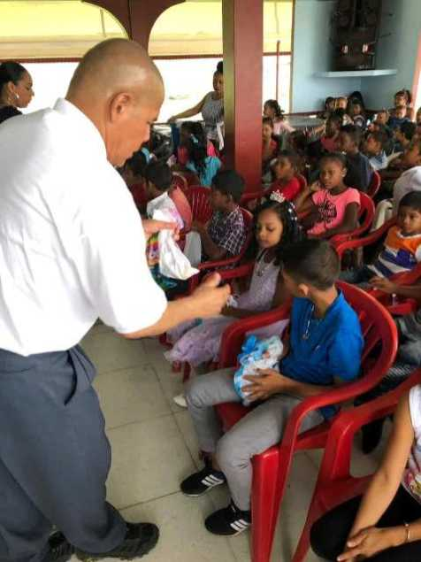 Minister Norton distributing goodies to the children of River's View, Region 10.