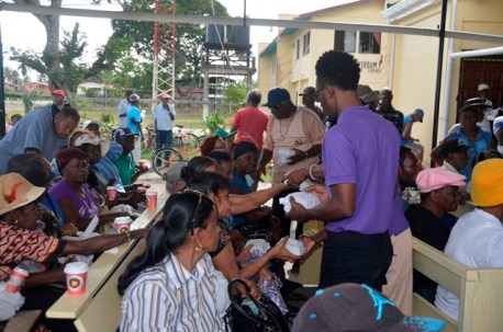Volunteers sharing the hot meals to the waiting pensioners.