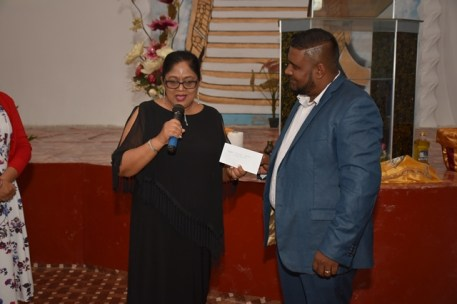 Mrs. Nagamootoo presents a gift to Pastor Seeram.