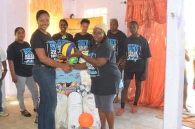 Olive Gopaul, Technical Officer within the Department of Social Cohesion hands over sports gear and equipment to Ms. Jennifer Williams, Headmistress of Baramita Primary School.