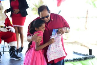 Prime Minister Moses Nagamootoo embraces a little girl as he presents her with a gift.
