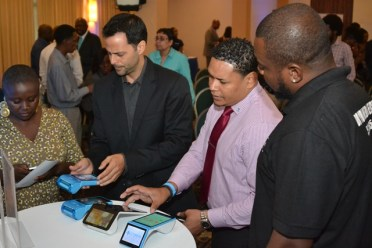 Participants at the launch of the WiPay app being show how it works.