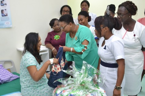 Minister Lawrence greets and hands over congratulatory hamper to Taysuwattie Budhu, mother of First Christmas baby at GPHC in the presence of nurses attached to the maternity unit.
