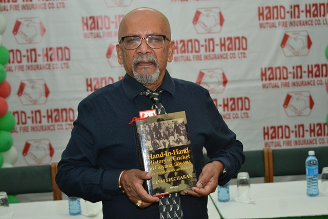 Professor Clem Seecharan displays the second volume of his book the History of Cricket in Guyana.