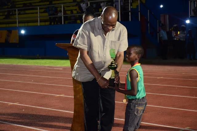 Minister of State, Joseph Harmon presents a prize to one of the winners of the Under 12 track and field events.