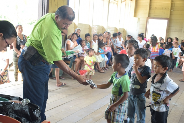 Minister of Indigenous Peoples' Affairs, Sydney Allicock handing over a toy to a child at Fairview Village, Region Nine.