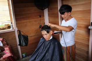 A HEYS youth entrepreneur at his barber shop at Four Miles, Region One