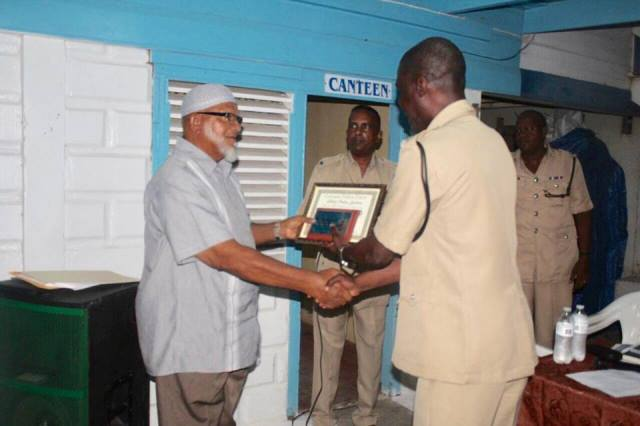 Religious leader and activist Mustapha Ali receives a plaque from Commander of B Division Paul Langevine.