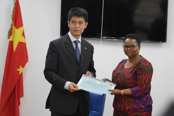 Minister of Public Health, Volda Lawrence receives a certificate which verifies the receipt of items from Hu Hanming, Economic and Commercial Counsellor, Embassy, People's Republic of China.