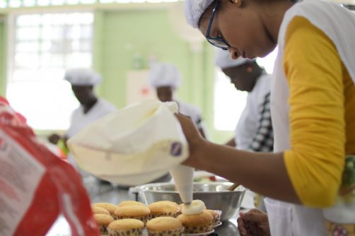 A teenage mother decorating a cake in preparation for her practical