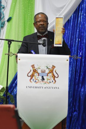 Vice Chancellor of the University of Guyana Professor Ivelaw Grffith holds up an outline of the Renaissance Project