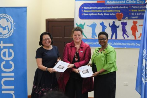 Sylvie Fouet, UNICEF Representative, Guyana & Suriname [centre] hands over copies of the Situation Analysis (SitAn) of Adolescent Pregnancy in Guyana to First Lady Sandra Granger and Minister of Public Health, Volda Lawrence.