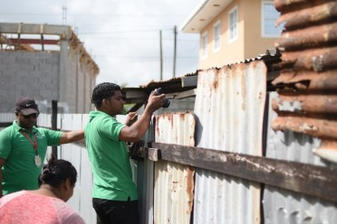 Officers of the EPA taking photographic evidence of the conditions under which pigs are being reared in the community of Lusignan.