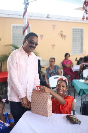 Attorney General Basil Williams Handing out gift to a child of the centre