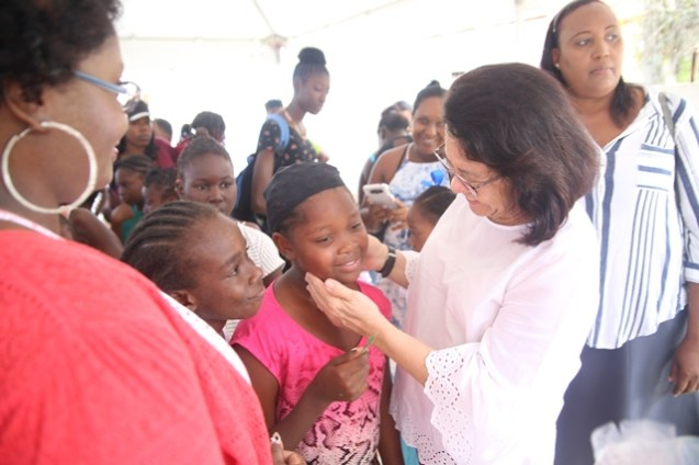 First Lady Sandra Granger interacts with two little girls from the community of Buxton.