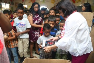 First Lady Mrs. Sandra Granger and Minster of Social Protection Amna Ally sharing gifts to children in Lusignan.