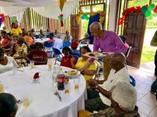 Minister of Communities Ronald Bulkan serving the seniors.