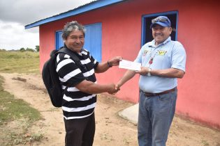 Minister of Indigenous Peoples' Affairs, Sydney Allicock handing over a cheque to Toshao of Shea Village, Francis Rufino