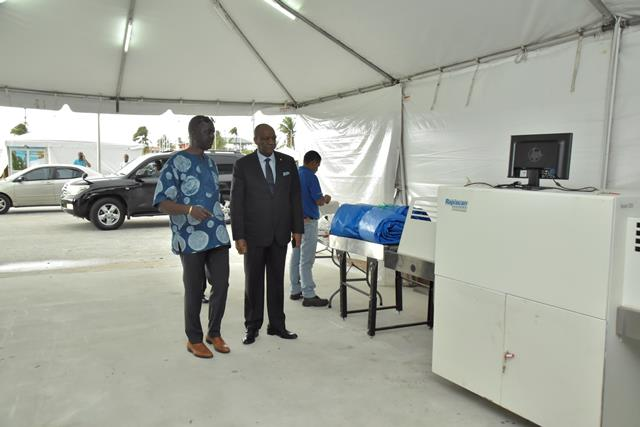 Minister of State, Mr. Joseph Harmon and Chief Executive Officer of the Guyana Lands and Surveys Commission, Mr. Trevor Benn look at of the bag scanners, which is being installed at the entrance of the Arthur Chung Convention Centre in preparation for the Seventeenth Session of the Committee for the Review of the Implementation of the United Nations Convention to Combat desertification (CRIC 17).