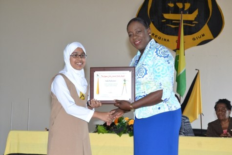 Minister of Education Dr. Nicolette Henry presenting eleven-year-old Queen's College student Naila Rahaman, her award.