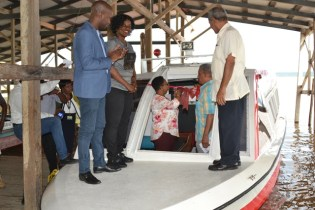 Minister of Public Health, Volda Lawrence and Regional Chairman, Gordon Bradford [standing in the boat] cuts the ribbon to commission the vessel while Regional Health Officer, Dr. Edward Sagala, Director of Regional and Clinical Services, Dr. Kay Shako and His Worship Gifford Marshall Mayor of Bartica look on.
