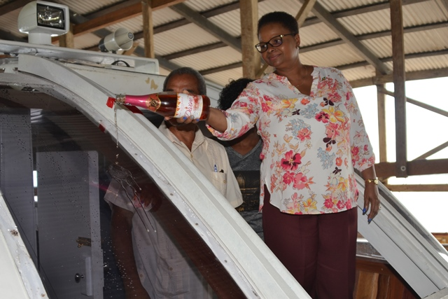 Minister Lawrence ceremoniously pours a drink to commission the vessel.