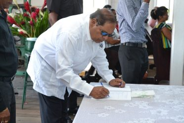 Prime Minister, Moses Nagamootoo signs the guest book as he arrived at the funeral service for Francis Vibert DeSouza's at the Meadowbank Catholic Church