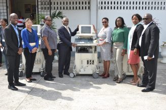 [In photo standing next to the machine on left] Minister of Foreign Affairs, Carl Greenidge and Minister of Public Health, Volda Lawrence [right] along with members of the diaspora and the two ministries